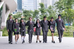 A group of Insworld Institute students in school uniform walking arm-in-arm smiling and happy.